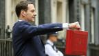 George Osborne mit seinem «Budget-Koffer». Statt tiefer Löhne, hoher Steuern und hoher Sozialzuschüsse will der neue Schatzkanzler - das Gegenteil.