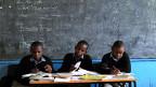 Drei Schüler einer Schule in Nairobi lernen am Tisch ihres Lehrers. Dieser ist abwesend - er streikt.