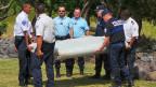 Beamte tragen das in La Réunion gefundene Wrackteil eines Flugzeuges weg. Nun wird untersucht, ob es zur verschwundenen Maschine der Air Malaysia gehört.