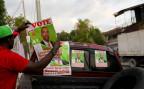 ein Mann verteilt Plakate eines Parlamentskandidaten in Port-au-Prince