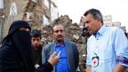 Eine schwarz verhüllte Frau erklärt Peter Maurer in den Ruinen eines Hauses in Sanaa, wie ihr Haus zerstört wurde.