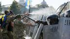 Polizeikräfte mit Helmen, Schilden und Schlagstöcken wehren vor dem Parlament in Kiew Demonstranten ab, die gegen die Verfassungsänderung sind.