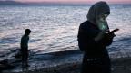 Ohne Smartphone wäre die Reise noch gefährlicher. Eine junge Frau hat nach der Überfahrt in einem Boot die griechische Insel Kos erreicht.