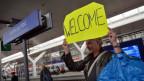 """Ein Passant heisst die Flüchtlinge auf der Durchreise nach Deutschland, am Salzburger Hauptbahnhof, am Samstag, 5. September 2015 mit einem Schild """"Welcome"""", willkommen."""