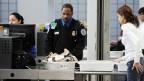 Beim Sicherheitscheck am Flughafen kontrolliert ein TSA-Mitarbeiter das Handgepäck