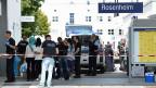 In Rosenheim, südlich von München, steht eine Gruppe von Flüchtlingen  Schlage, sie werden registriert.