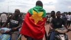 Burkina Faso war bis 1960 als Obervolta Teil Französisch Westafrikas. 1984 gab die Regierung dem Land den neuen Namen Burkina Faso, was mit «Land der Unbestechlichen» übersetzt wird. Der Demonstrant hat sich die Flagge von Burkina Faso um die Schultern gelegt.
