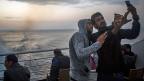 Filmen an Bord einer Fähre, die Flüchtlinge von der griecheischen Insel Lesbos in den Hafen von Piräus bringt.