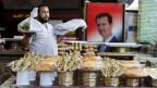 Ein Verkäufer in weissem Berufskittel verkauf syrische Süssigkeiten. Neben ihm an der Wand hängt - Bashar al-Assad