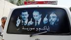 Putin will in New York die USA für seine neue Koalition gewinnen. Bild: Ein Kleinbus in Latakia zeigt ein Plakat mit dem syrischen Präsidenten Bashar al-Assad, dem russischen Präsidenten Putin und dem libanesischen Hisbollah-Führer Hassan Nasrallah.