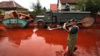 Über eine Million Kunikmeter des roten Schlamms haben Anfang Oktober 2010 das Dorf Devecser überschwemmt. Bild: Freiwilliger Helfer bei den Aufräumarbeiten.
