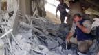 Zivilisten betrachten die Zerstörung, die der russische Luftangriff im Norden von Syrien verursacht hat.