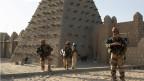 Französische Soldaten bewachen den Eingang der Sankoré-Moschee in Timbuktu. Sie stammt aus dem 14. Jahrhundert. Mit Hilfe der UNESCO wurde ein Programm zur Konservierung aufgelegt. Drei weitere Moscheen aus dieser Zeit, die El-Hena-Moschee, die Kalidi-Moschee und die Algourdour-Djingareye-Moschee, sind zerstört.