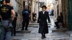 Ein orthodoxer Jude läuft durch die Altstadt von Jerusalem. Den Palästinenser ist der Zutritt verboten.