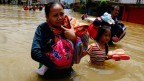 Menschen tragen ihre Habseligkeiten durch das Hochwasser in Java, Indonesien.