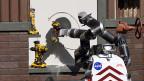 Darpa-Roboter-Wettkampf im vergangenen Sommer. Auf dem Bild ein humanitärer Einsatz - ein Roboter bohrt ein Loch in eine Mauer, um eingeschlossen zu befreien,e