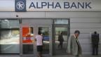 Ein Mann geht in Athen an einer Filiale der griechischen Alpha-Bank vorüber