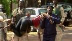 Eine verletzte Geisel wird von Sicherheitskräften aus dem Radisson Hotel, Bamako, Mali, getragen. Mindestens 170 Personen wurden als Geiseln festgehalten.