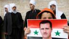 Die Drusen befürchten, dass sich Präsident Bashar al-Assads aus dem Drusengebiet zurückziehen wird. Ein Drusen- Junge hält eine syrische Fahne mit dem Bild von Syriens Präsident Bashar al-Assad.