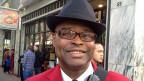 Wayne Francis Alexis in schwarzem Hut und rotem Anzug; er ist einer von fünf Botschaftern vom Union Square. Im Auftrag der Geschäfts-Vereinigung dieser Einkaufsdestination in San Francisco begrüssen die Botschafter Besucherinnen und Besucher, weisen ihnen den Weg und geben gratis Stadtpläne ab.