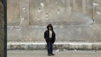 «Weiterarbeiten für die Menschen, die noch am Leben sind», sagt Azad. Symbolbild: Ein syrischer Junge steht vor einer zerbombten Schule.