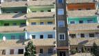 24 Wohnungen in einem Dresdener Plattenbau. Sechs junge Männer, Flüchtlinge, leben in der Wohnung mit dem orangenen Balkon rechts oben im Bild. Obwohl die Durchmischung von Einheimischen und Flüchtlingen eigentlich ideal ist, grüsst man sich aber kaum.