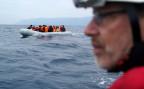 ein Freiwilliger beobachtet ein Flüchtlingsboot vor der Küste von Lesbos