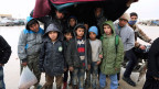 Syrische Flüchtlinge versuchen, sich vor dem kalten Regen zu schützen.