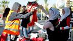 Freiwillige verteilen in den Strassen von Tripolis warme Winterkleider.