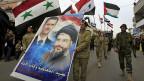 Die Hisbollah hat ein strategisches Interesse daran, dass der iranfreundliche Assad in Syrien an der Macht bleibt. Das sichert der Hisbollah die Nachschublinien zu ihrem Sponsor Iran. Bild: Bei der Beisetzung eines Hisbollah-Kommandanten tragen Mitglieder der Baath-Partei am 2. März ein Bild des syrischen Präsidenten Assad zusammen mit dem Hisbollah-Führer Nasrallah.