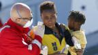 Ein Helfer betreut eine Flüchtlingsfrau und ihr Kind bei der Ankunft in Sizilien.