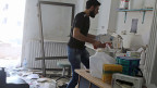 Ein Mann sammelt in einem zerbombten Raum im Spital von Mödecins sans Frontières in Aleppo Medikamente zusammen