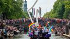 Menschen in Gruppen seien unachtsamer, frecher und verursachten viel mehr Lärm, sagt eine Amsterdamerin. Nicht nur Amsterdams Rotlichtviertel zieht viele Touristen an, Menschenmassen gibt es auch anlässlich der Kanal-Parade (Bild).