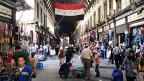 Im Zentrum von Damaskus, im grossen Markt, kann man den Krieg für einen Moment lang vergessen. Die Innenstadt ist intakt, die Waffenruhe hat auch der Hauptstadt Erholung gebracht. Die Leute sind auf der Strasse, die Schulen sind geöffnet, die Kehrrichtabfuhr funktioniert, Polizisten regeln den Verkehr. Die Regierung bemüht sich, den Anschein von Normalität aufrechtzuerhalten.