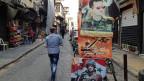 Patriotische Slogans: Assad wird auf Plakaten als Beschützer des Vaterlands gefeiert. Das Regime bezahlt auch im sechsten Kriegsjahr noch Löhne und Renten, hält die Institutionen aufrecht, so gut es geht. Der Staat verschuldet sich dafür tief.