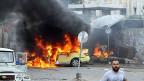Mindestens 48 Menschen sind laut der syrischen Beobachtungsstelle für Menschenrechte in der syrischen Küstenstadt Tartus umgekommen. Bild: Flammen schiessen aus einem Auto an einer Bushaltestelle in Tartus.