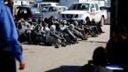 Afrikanische illegale Einwanderer warten in einem Hafen in Tripolis, Libyen, auf Hilfe, nachdem aus Seenot gerettet wurden.