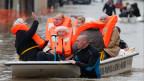 Feuerwehrmänner evakuieren Bewohner aus einem überfluteten Gebiet nach schweren Niederschlägen in Frankreich.