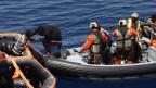 Helfer retten Flüchtlinge aus Seenot.