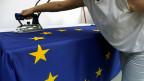 Eine Serbin bügelt eine Flagge der EU.