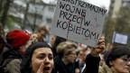 «Beenden wir den Krieg gegen die Frauen» steht in polnischer Sprache auf dem Plakat einer jungen Demonstrantin in Warschau.
