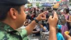 «Wir haben das Recht zu protestieren! Wir verstossen gegen kein Gesetz!» Eine kleine Gruppe demonstriert mit Postern vor dem Militärgericht in Bangkok. Ein Polizist fotografiert die Demonstranten, ein anderer fordert sie bald auf, zu schweigen.