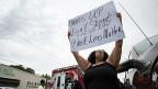Nach einer Gedenkfeier für den erschossenen Alton Sterling protestiert eine Frau mit einem Transparent: «Hands up. Don't shoot. Black Lives Matter.»