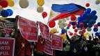 Eins zu null für die Philippinen. Das Haager Schiedsgericht sieht Chinas Ansprüche im südchinesischen Meer als ungerechtfertigt. Bild: Aktivisten von den Philippinen feiern in Manila mit bunten Ballonen den Schiedsspruch aus Den Haag.