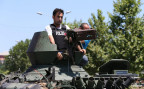 ein Panzer der Armee wird von Polizisten weg gefahren