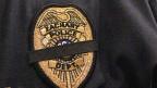 Schwarzes Trauerband über dem Emblem auf der Uniform eines Polizisten in Baton Rouge.