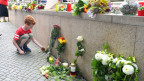 Eine Knabe legt Blumen in der Nähe des Tatorts in München nieder.