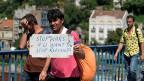 «STOP WARS IF U WANT TO STOP REFUGEES», steht auf dem kleinen Plakat eines Mannes in einer Flüchtlingsgruppe in Belgrad.