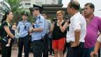 Die Ehefrau eines der verhafteten Bürgerrechtler, wird von einem Polizisten befragt; sie wartet mit anderen Aktivisten auf das erste Urteil.