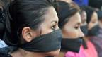 Zwei Frauen mit schwarzen Bändern vor dem Mund, protestieren gegen die Massenvergewaltungen in Indien.